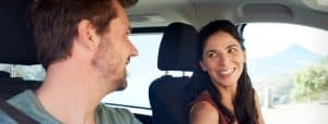 Happy mid adult white couple driving in their car, smiling at each other, close up, side view
