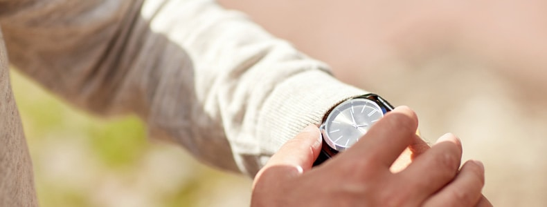 Man checking time on wristwatch outdoors