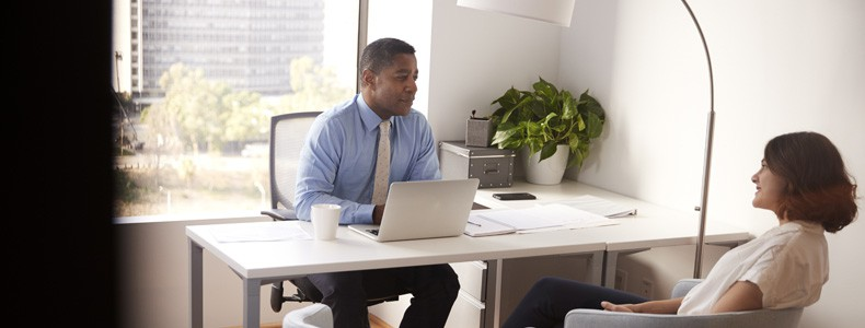 Lawyer In Modern Office Sitting At Desk Meeting Female Client