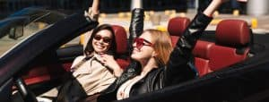 Cheerful girls joyfully spending time together driving on holiday