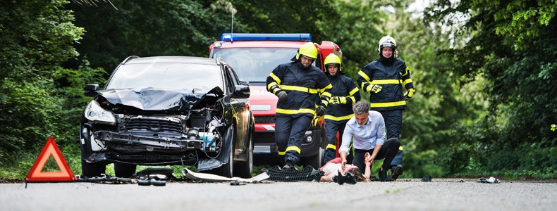 Firefighters running to rescue a woman lying unconscious on the road after a car accident