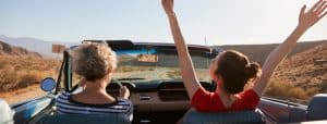 Mum driving car, daughter with hands in the air